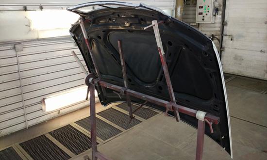 Установка капота Audi A4 на штативе в покрасочной камере в Нижнем Новгороде. Кузовной центр GutWagen.
